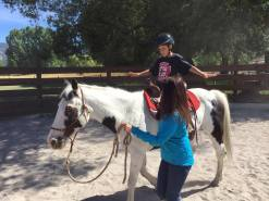 Andy, learning to ride on his soon to be adopted horse Maverick